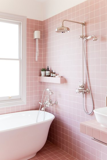 pink bathroom with freestanding bathtub and exposed plumbing