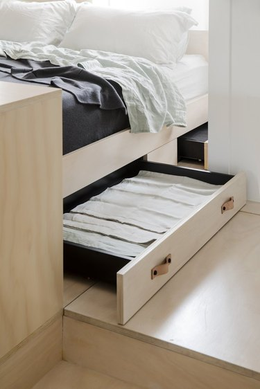 A built-in drawer beneath a bed
