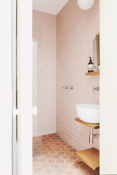 bathroom with pink subway tile and floating vessel sink