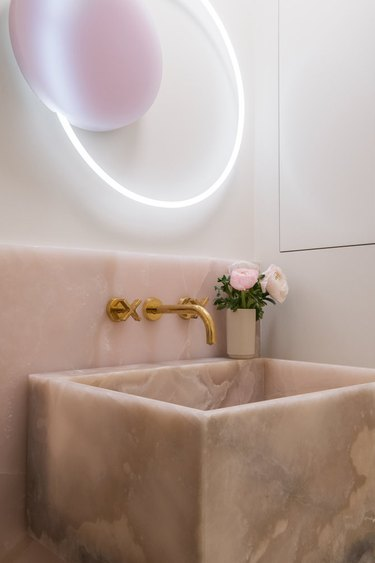 bathroom with pink onyx backsplash and sink