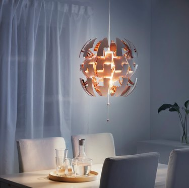 Copper and white contemporary dining room lighting from IKEA above table