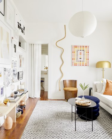Contemporary apartment with gold vertical wall art and gallery wall