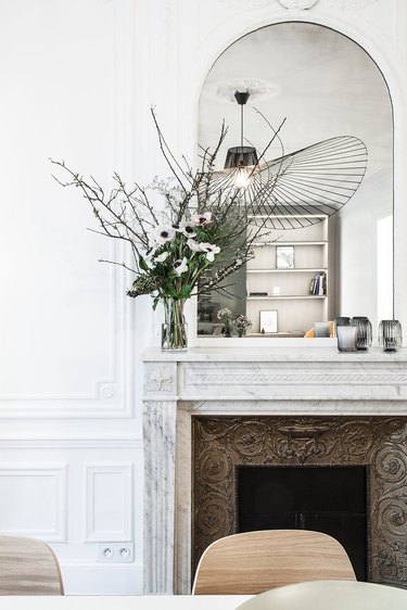 Contemporary apartment with antique fireplace and current light fixture