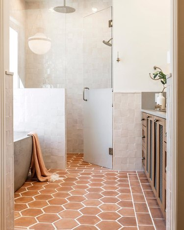 contemporary shower with terra cotta floors and glass shower door