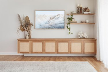 family room storage with wood built in credenza with flat screen tv, and wood floors.
