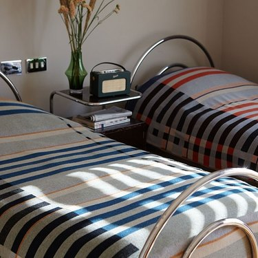 two beds with striped blankets and metal night stand in between