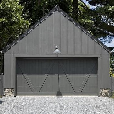 weathered gray wooden garage doors with wall sconce above