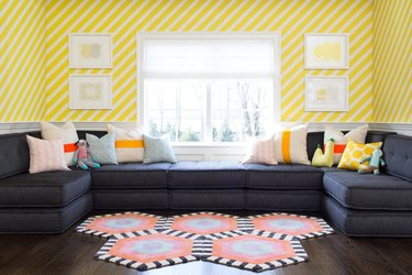 living room wallpaper idea with graphic yellow stripe installed diagonally