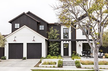 white and black exterior with black garage doors