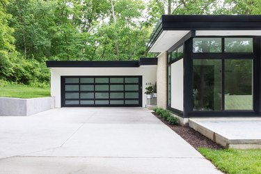 midcentury home with black garage doors with window panes