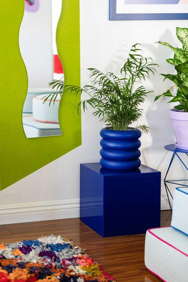 Blue planter and plant next to colorful decor