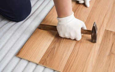 Installing laminated floor, detail on man hand in white gloves holding hammer over wooden tile, foam base layer under