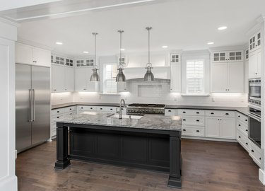 beautiful kitchen in new luxury home with island, pendant lights, stainless steel appliances, and hardwood floors
