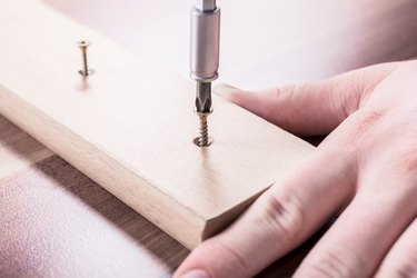 Craftsman Driving A Screw Into A Piece Of Wood
