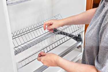Installing wire dish rack for drying dishes inside kitchen cabinet.