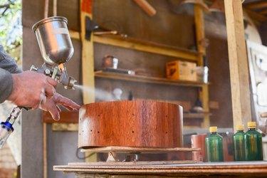 Carpenter spraying lacquer on merbau wood drum shell