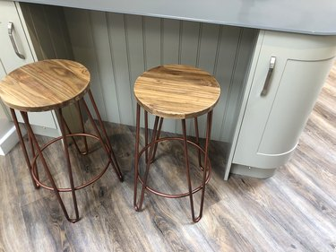 Image of curved kitchen floor cabinets painted duck egg blue, breakfast bar / kitchen island tongue and groove cladding timber, grey composite corian worktop countertop, oak wood stools with copper coloured metal legs on dark oak effect laminate floors