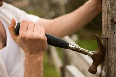 Farmer pulling nail from fencepost with hammer.
