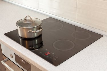 Metal steel saucepan in modern kitchen with induction stove
