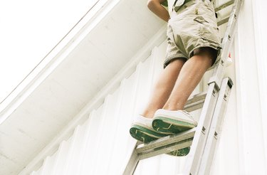 Man standing on ladder, low angle view