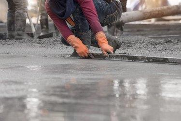 Construction worker troweling wet concrete.