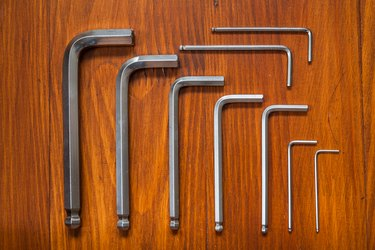 Set of hexagonal keys on a wooden background. Knolling style shot.