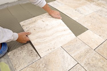 Worker Places New Marble Tile on a Bathroom Floor