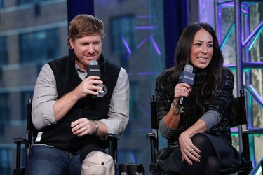 Chip and Joanna Gaines sitting in chairs holding microphones