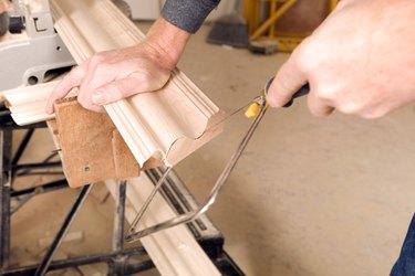 Carpenter Using a Coping Saw to Cut Trim End