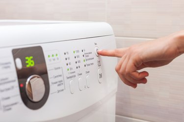 Young woman or housekeeper select the program on washer