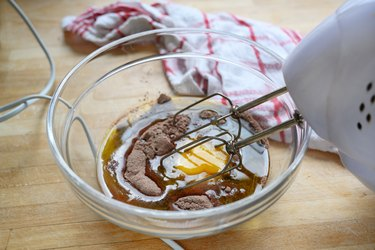 electric mixer in a glass bowl with cake dough of egg, cocoa and flour on a wooden table with a kitchen towel, baking concept
