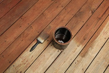 Partially stained deck; paint brush and a can of stain