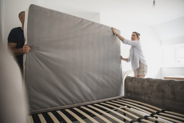 Couple Setting Up Bed Together in New Home