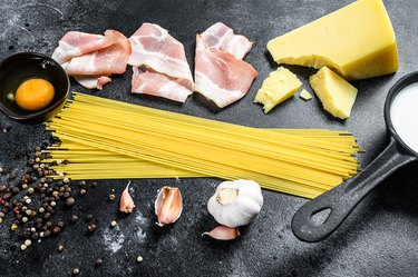 Ingredients for traditional italian pasta alla carbonara. Uncooked spaghetti, pancetta bacon, parmesan cheese, egg. Black background. Top view