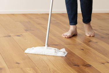 Feet of young woman mopping the floor of wood