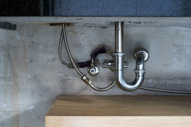 Bathroom steel sink pipes, trap and drain on concrete wall