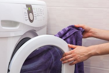 Woman loading laundry to the washing machine