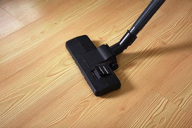 Old vacuum cleaner on parquet floor with copy space