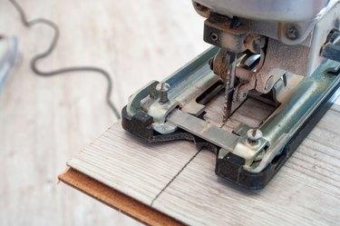 Electric jigsaw at work. Closeup.