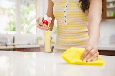 Hispanic woman spraying and wiping counter
