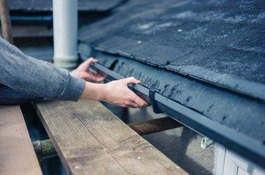 Hands of worker fixing drain