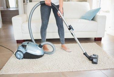Woman hoovering rug