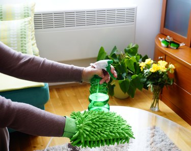 Home cleaning products, sponge and detergent in women hands that clean the glass table