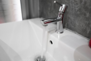 Running water from modern stainless steel faucet in white sink. Counter bathroom interior contemporary. Luxury and stylish design bathroom with a concrete style walls.