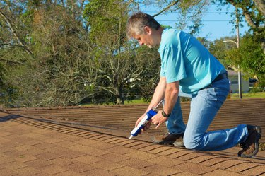 Homeowner patching roof with caulk gun protection from rain storms