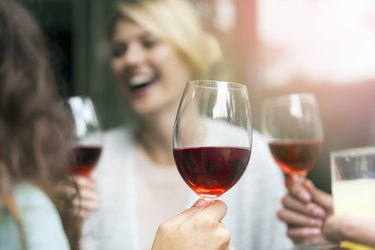 Wineglass held by woman during social gathering