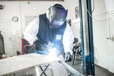 Car body shop technician using a MIG welder to repair a damaged car part in a car body shop