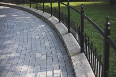 Wrought-iron fence and curved stone driveway.