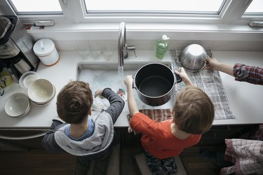 Overhead view brothers doing dishes at kitchen sink