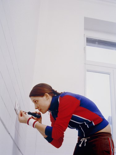 Young Woman Fixing Electrical Outlet